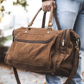 Hamosons, 696 - Mittelgroße, braune Reisetasche aus Leder, Modell 696, Mann hält Tasche an den Griffen und geht einen Weg entlang - 08