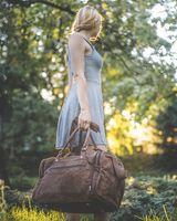 Hamosons, 696 - Mittelgroße, braune Reisetasche aus Leder, Modell 696, Frau hält Tasche an den Griffen und steht in der Natur- 04