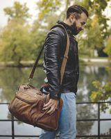 Hamosons, 696 - Mittelgroße, braune Reisetasche aus Leder, Modell 696, Mann trägt Tasche über die Schulter und geht an einem See vorbei- 04