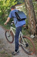 Jahn-Tasche, 670 - Großer, schwarzer Lederrucksack bzw. Lehrerrucksack, Mann hat Rucksack auf und sitzt auf Rad - 06