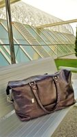 Jahn-Tasche, 697 - Große, cognac-braune Reisetasche aus Leder, Modell 697, Tasche steht auf Bank außerhalb Flughafen - 05