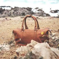 Jahn-Tasche, 698 - Kleine, cognac-braune Reisetasche aus Leder, Modell 698, Tasche steht am Strand mit Wasser im Hintergrund - 07