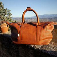Jahn-Tasche, 698 - Kleine, cognac-braune Reisetasche aus Leder, Modell 698, Tasche steht auf Steinmauer mit Blick ins Umland - 04