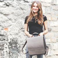Jahn-Tasche, 670 - Großer, grauer Lederrucksack bzw. Lehrerrucksack, Frontansicht, Frau hält Rucksack in den Händen vor einer Mauer - 08