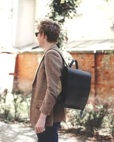 Jahn-Tasche, 668 - Mittelgroßer, schwarzer Lederrucksack bzw. Lehrerrucksack, Schrägansicht, von Mann über einer Schulter getragen - 08