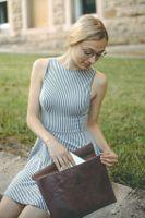 Jahn-Tasche, 1042-cw - Braune A4 Aktenmappe bzw. Dokumentenmappe, Frau sitzt auf Mäuerchen, Mappe steht daneben und sie holt etwas aus der Mappe heraus - 09