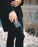 Jahn-Tasche, 012 - Exklusives Federmäppchen bzw. Lederetui aus Büffelleder in Schwarz, Mäppchen von Frau in Außenumgebung in Hand gehalten - 09