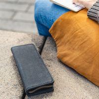Jahn-Tasche, 012 - Exklusives Federmäppchen bzw. Lederetui aus Büffelleder in Schwarz, Mäppchen liegt geschlossen neben draußen sitzender Frau - 07
