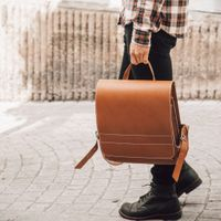 Jahn-Tasche, 668 - Mittelgroßer, cognac-brauner Lederrucksack bzw. Lehrerrucksack, Mann trägt Rucksack in der Hand am Tragegriff - 09