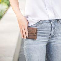Branco, 35250 - Kleine Geldbörse bzw. Kleines Damen-Portemonnaie in Braun, Frau hat Börse in der Hand neben Hosentasche - 05