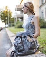 Hamosons 560 - Großer, anthrazit-grauer Lederrucksack bzw. Laptop-Rucksack aus Nappaleder, Frau sitzt auf Mäuerchen an einer Straße, Rucksack steht daneben - 05