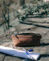 Jahn-Tasche, 010 - Schlampermäppchen aus Büffelleder in Braun, Mäppchen steht geöffnet auf Steinmauer, daneben Schreibzeug liegend - 12