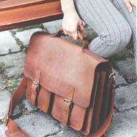Jahn-Tasche, 420-n  – Robuste braune Aktentasche bzw. Lehrertasche, Frau sitzt draußen auf Holzbank mit Tasche neben sich, Detailaufnahme Tasche I - 11