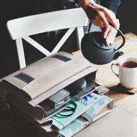 Jahn-Tasche, 668 - Mittelgroßer, beige-grauer Lederrucksack bzw. Lehrerrucksack, Rucksack liegt geöffent auf Tisch, daneben gießt jemand Tee ein - 08